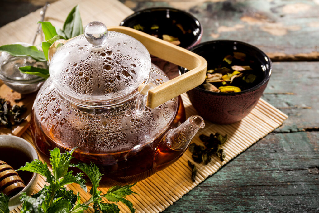 Beautiful Tea Ceremony Glass Teapot Honey Mint Cups on Old Rustic Green Table Background Closeup Horizontal
